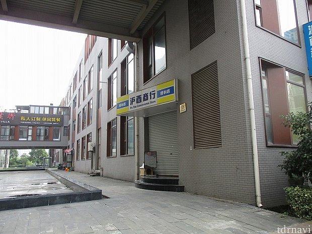 ホテル正面入り口から敷地内道路の反対側の建物のコンビニ