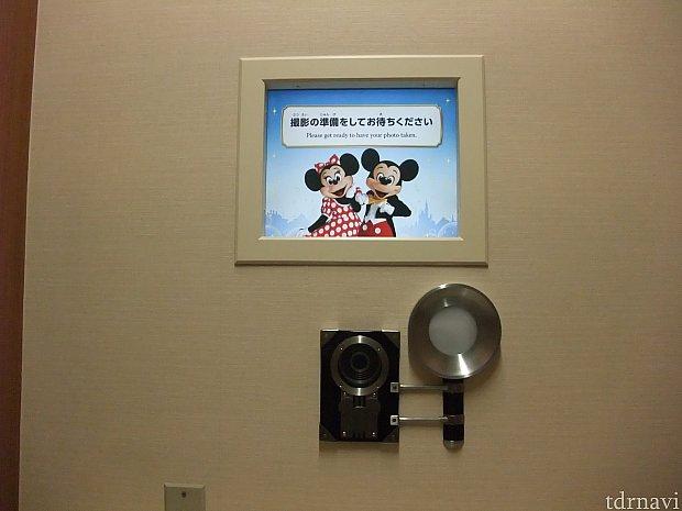 前面にモニターとカメラがあり、ミッキーとミニー、東京ディズニーランドと東京ディズニーシーのシンボルがシルエットになっています!? カメラにもミッキーの形が!? このカメラの下のテーブルに小さな書類を差し出す窓があり、そこから年間パスポート作成申込書と本人確認書類を渡します。 窓からはキャストさんの手しか見えませんが、マイクを通してお話ができます。 申込や記載内容の確認をします。