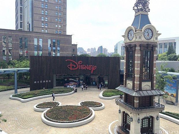 """ディズニーストア上海です。お店の前にはミッキーの形の花壇、ミッキーの時計台があります。中国語の店名は『迪士尼旗舰店』、""""ディズニーフラッグシップ店""""です。後ろに見える建物は上海税関です。"""