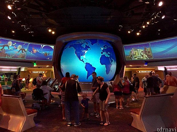 アトラクション終了後のゲームエリア。地球儀の両側の大画面にゲストの顔写真が映し出されています。