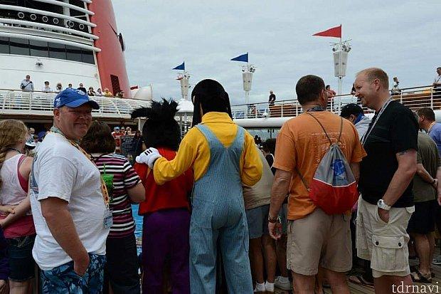 グーフィーとマックスが子どもたちが作った船を浮かべるところを見学中