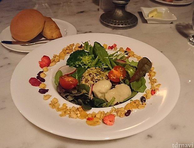 友人の前菜はサラダ。とりどりの野菜に豆と穀物が入ってます。お皿の周りにはグラノーラとドライフルーツ。パンも美味しかったです。モチモチした米粉パンに、パリッとした皮のライ麦パン。