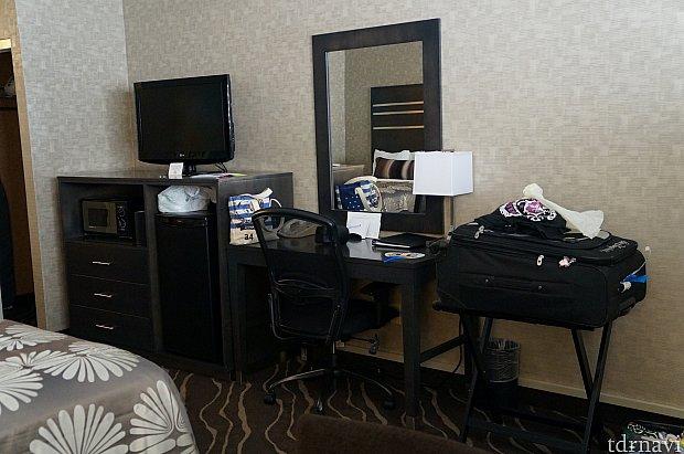 テレビの下に大きめ冷蔵庫と服などを入れるキャビネット。大きな机のドレッサーもあります。