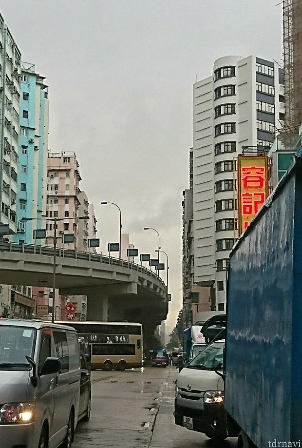 右側のラウンドした窓が沢山ある白い建物がホテル。道路の真ん中から向かってくる、青と紫のバスが、エアポートエクスプレス・シャトルバス🚌
