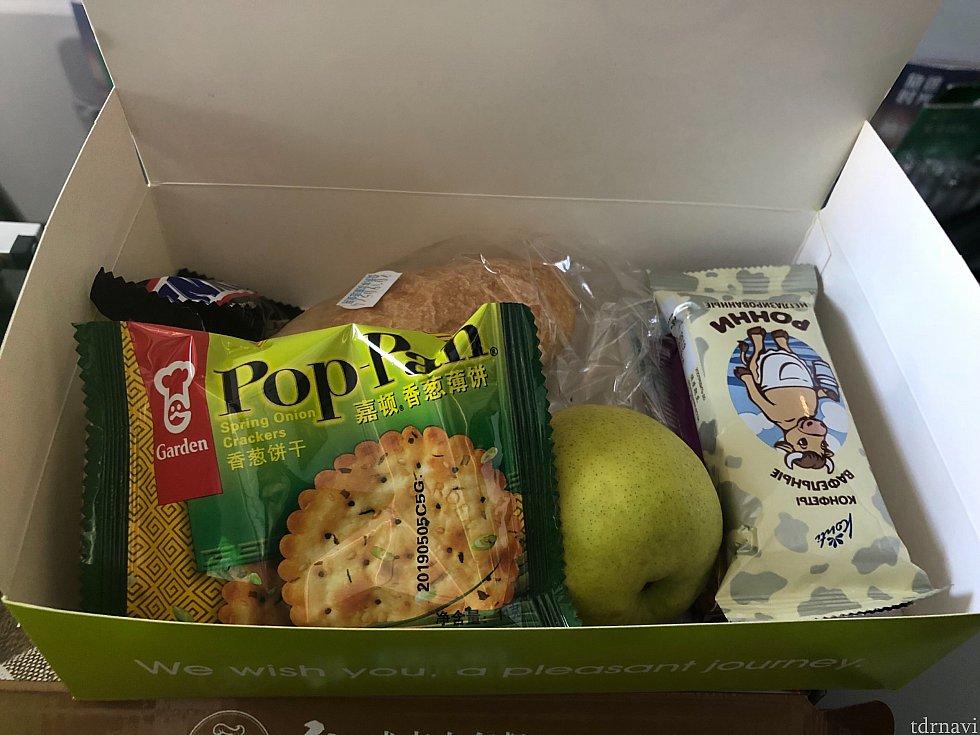 行きの機内食。お菓子、パン、フルーツ。