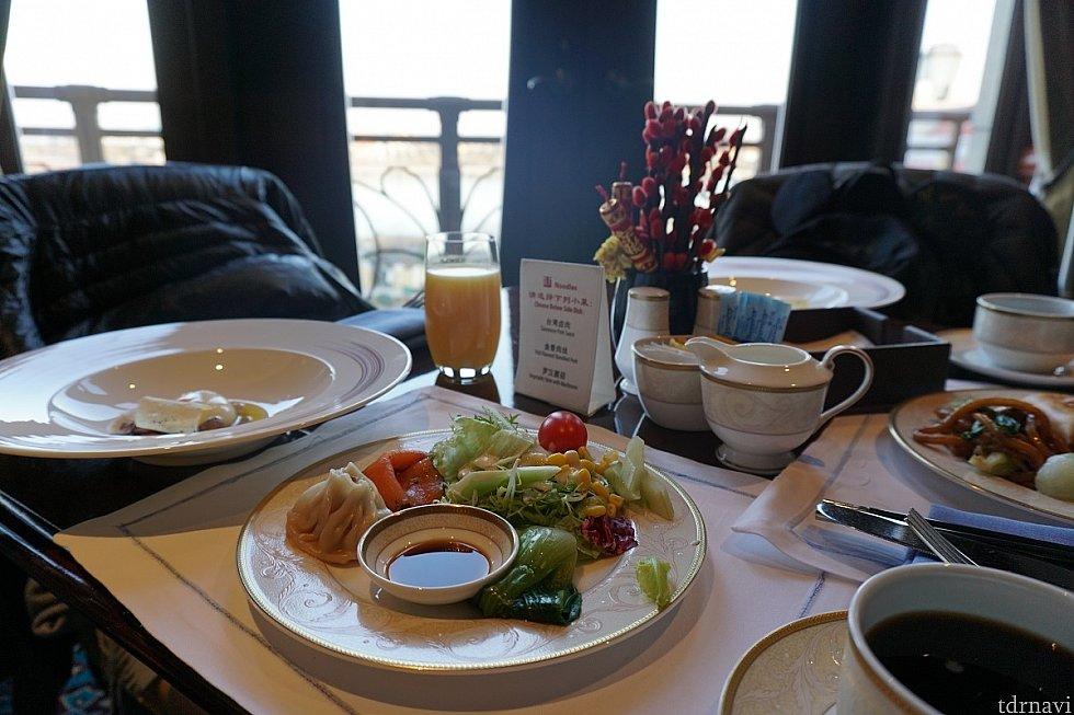 クラブラウンジの朝食、左が温泉卵withポルチーニ。窓からはパーク見えます、朝正面入り口に向かう人々の様子でその日の混み具合が予想できると思います。