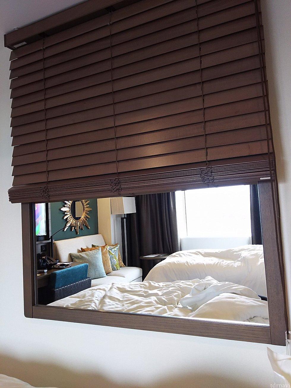 ベッド横の壁に鏡。木製ブラインドで隠すことが出来ます。