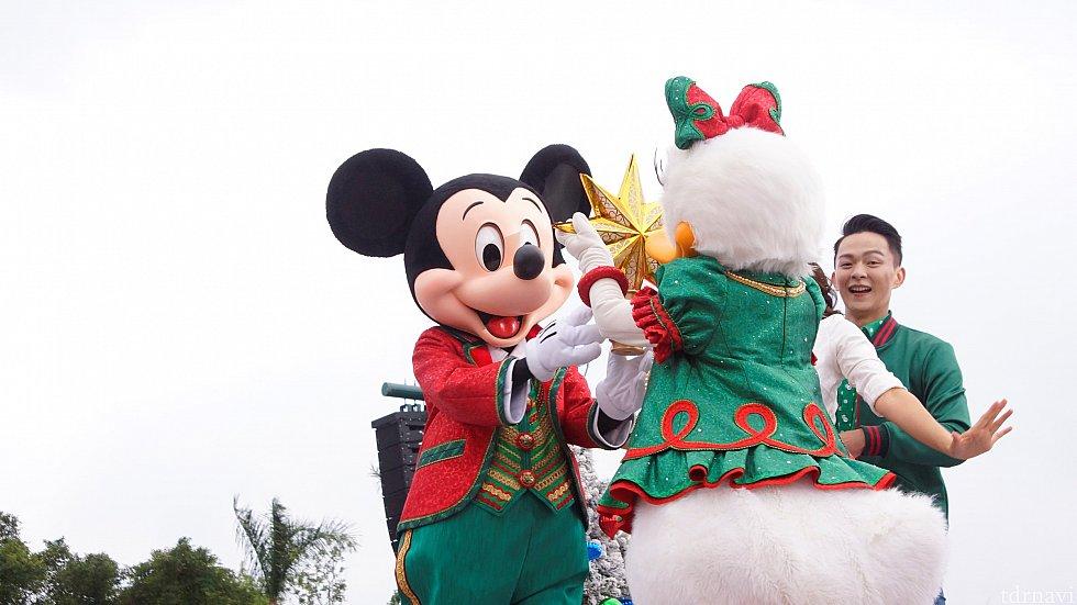 デイジーがミッキーにクリスマスツリーには欠かせない物を渡します。