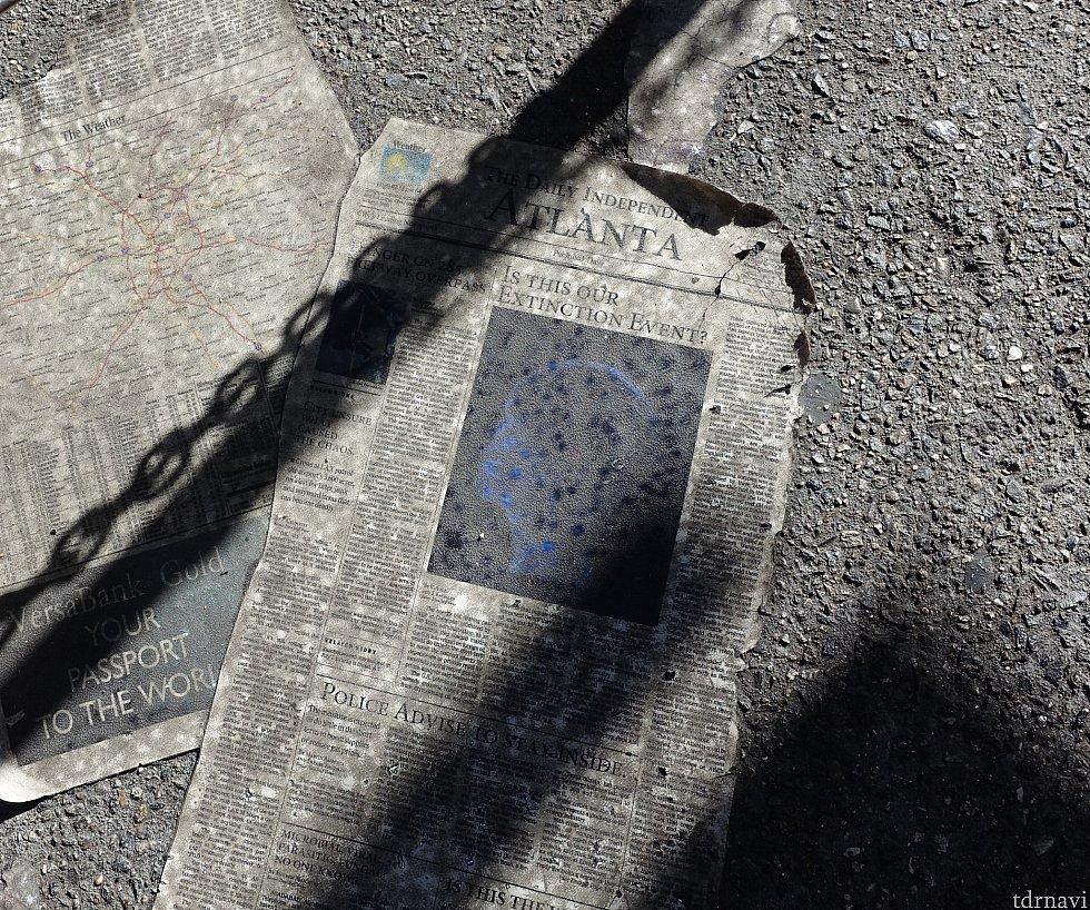 足元には新聞が散乱しています。