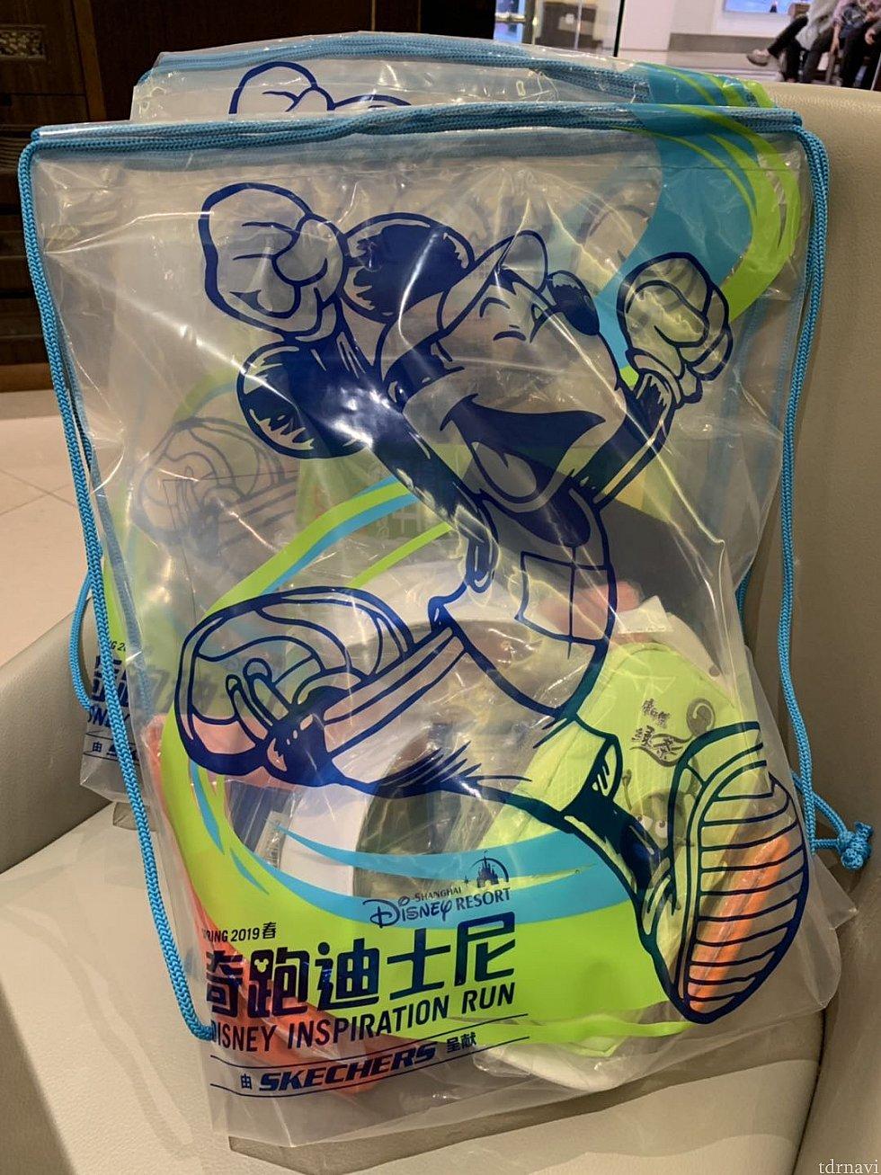 透明のリュック型のビニール袋にゼッケンやその他の物が入っています。