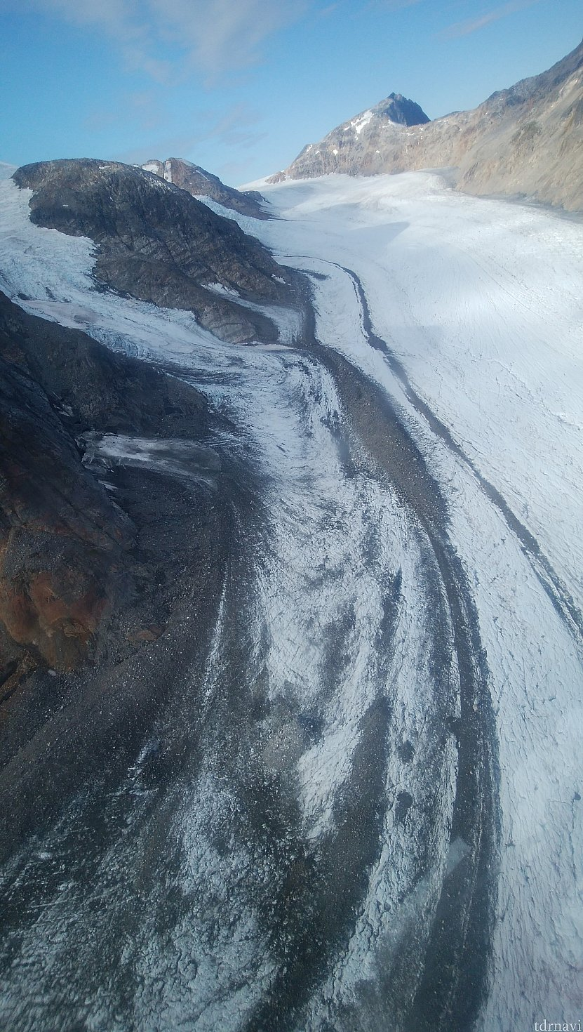 氷河のシマ模様、崩れた岩石が氷河上に溜まり、氷河の流れと共に少しずつ下流に流れていくためできるそうです。