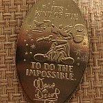 ウォルトディズニーのサインが描かれたクォーターのスーベニアメダル。