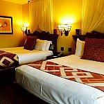 お部屋のベッド。なかなかの広さで、アースカラーの落ち着いた色調でまとめられています。
