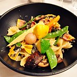 Farfalle pasta, grilled mushrooms with truffle oil sauce, and young vegetables