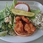カニのパテに、シュリンプのフライのバーガー。レタス、トマト、オニオン、ピクルスを添えて。サイドはシーザーサラダとコールスローサラダ。